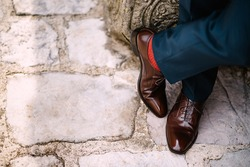 Crossed legs of a man in blue pants, red socks and brown shoes standing on the stone road, top view