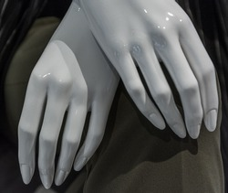 crossed mannequin hands on gray backgtound