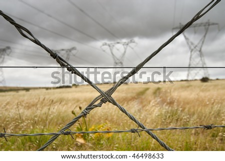 Crossed wire from a gate in the foreground with four electricity pylons standing ina dry landscape in the background