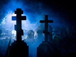 Crosses and tombstones silhouettes in the blue foggy night