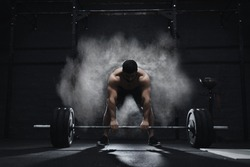 Crossfit athlete preparing to lift heavy barbell in a cloud of dust at the gym. Barbell magnesia protection.