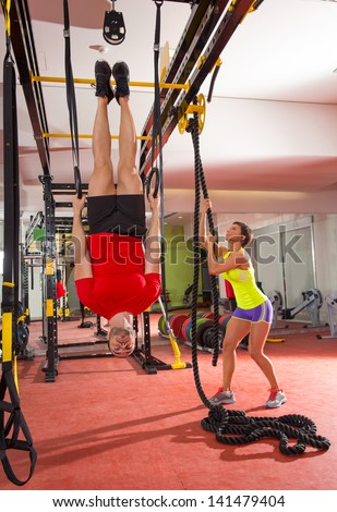 Crossfit fitness dip ring man workout upside down at gym dipping ans woman with rope