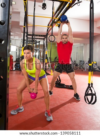 Crossfit fitness Kettlebells swing exercise man and woman workout at gym