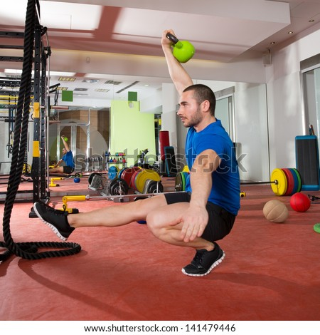 Crossfit fitness man balance Kettlebells with one leg exercise at gym workout
