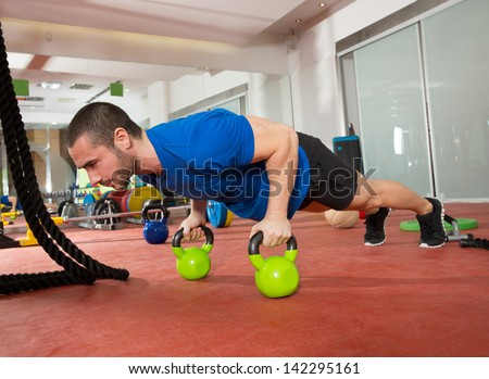 Crossfit fitness man push ups Kettlebells pushup exercise at gym workout