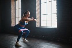 Crossfit healthy concept. Woman wearing sport clothing using resistance band