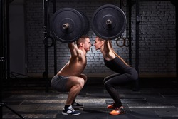Crossfit lifting bar by woman and man in group workout against brick wall.
