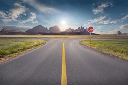 Crossing with stop sign towards the sun and mountain peaks with yellow line on asphalt. Success and vision concept.