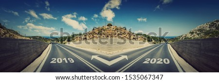 Crossroad concept, road split in two different ways. Choose to remain in the 2019 year or move forward to 2020 new life challenges. Difficult decision, live in the past or change your future.