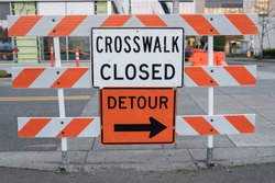 Crosswalk closed and detour signs on the barricade blocking the intersection.