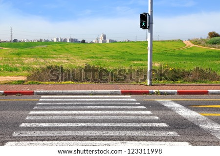 Crosswalk leading to green meadow and a new town on the horizon