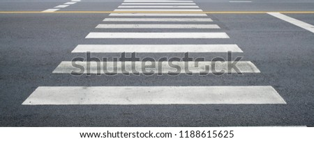 crosswalk on the road for safety when people walking cross the street, Pedestrian crossing on a repaired asphalt road, Crosswalk on the street for safety.