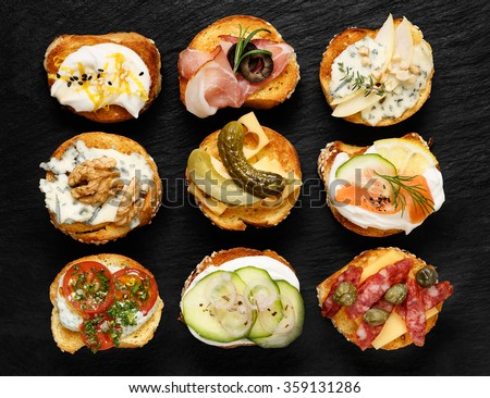 Crostini with different toppings on black background. Delicious appetizers