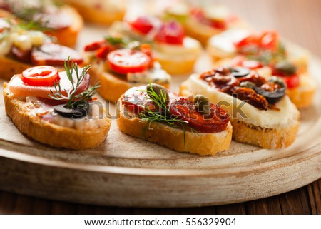 Crostini with different toppings on wooden background. Delicious appetizers. Front view.