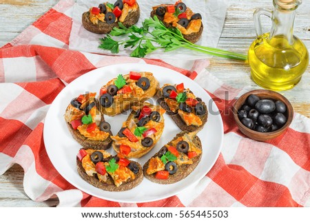 Crostini with pieces of mackerel fish, rings of black olives, red bell pepper on white plate on kitchen cloth, view from above, bottle with cooking oil and parsley on background, close-up