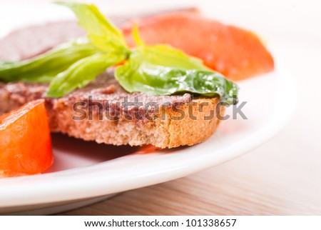 Crostinis with olive tapenade, basil and tomato on plate