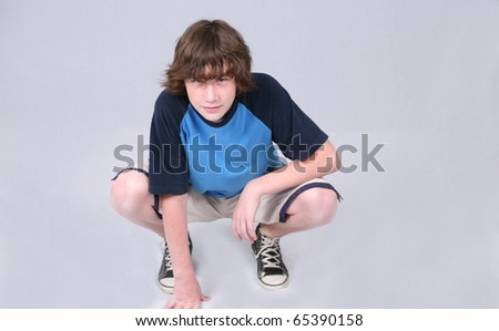 crouching preteen boy with freckles in studio