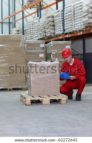 crouching worker checking inventory stocks at a factory storeroom.