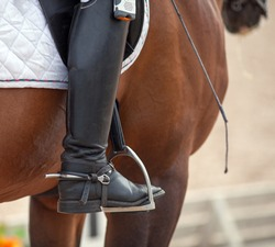 Croup of a red horse with a white saddle and a rider's foot in a boot with a spur inserted in a stirrup. Equestrian sport.