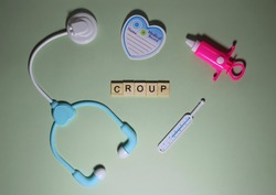CROUP word made from wooden cube on light green background surrounded by set of toy medical equipment . Selective focus, top view.