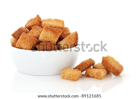 Crouton stack in a porcelain bowl and scattered isolated over white background.