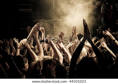 Crowd at a concert, audience raising hands up