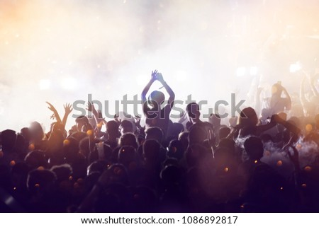 Crowd at concert - Cheering crowd in front of bright colorful stage lights #1086892817