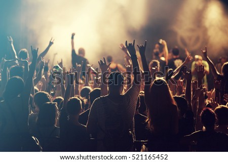 Shutterstock Crowd at concert - Cheering crowd in front of bright colorful stage lights