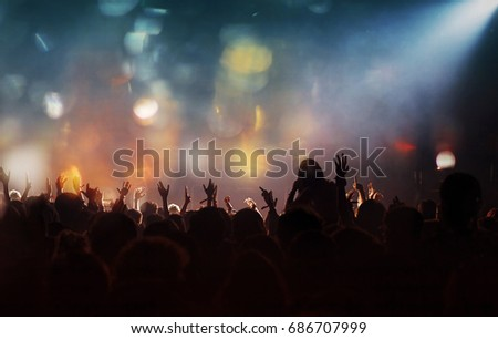 Crowd at concert - Cheering crowd in front of bright colorful stage lights #686707999