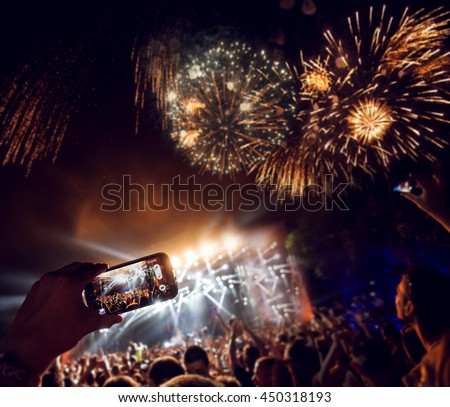 Crowd at concert looking at firework. Focus is on smart phone. #450318193