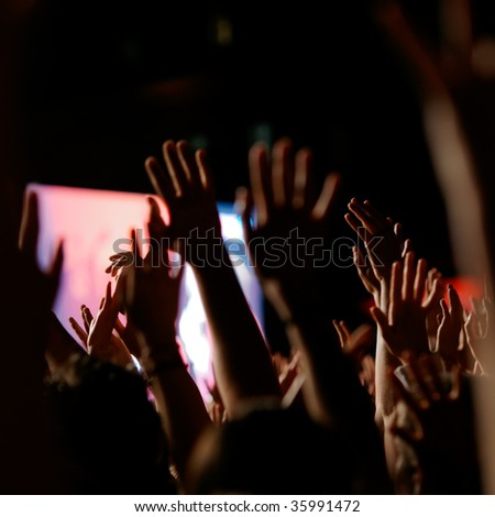 Crowd cheering at a concert. Back-lit.