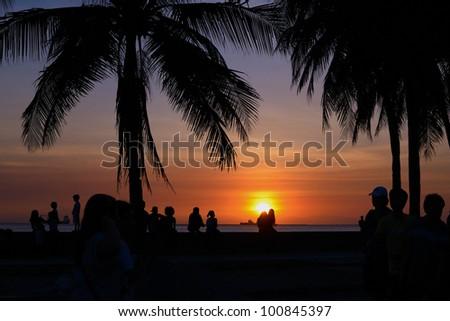 crowd enjoying a beautiful sunset at manila bay.