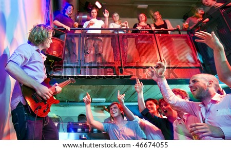 Crowd going wild during a live performance of a guitarist in a club