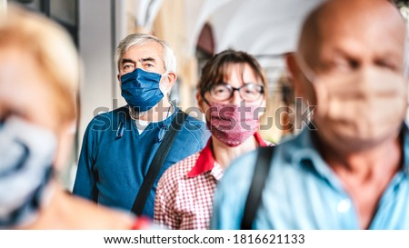Crowd of adult citizens walking on city street - New reality lifestyle concept with senior people with covered faces - Selective focus on bearded man with blue protective mask