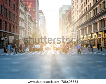 Crowd of anonymous people crossing the street at a busy intersection in Manhattan, New York City with the bright glow of sunset in the background