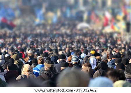 Crowd of anonymous people on street in city center, selective focus