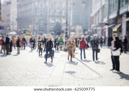 Crowd of anonymous people walking on busy city street