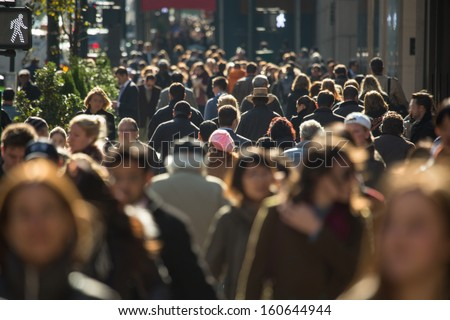 Crowd of anonymous people walking on busy New York City street