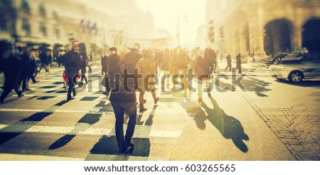 Crowd of anonymous people walking on sunset in the city streets