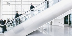 crowd of blurred business people rushing on escalators