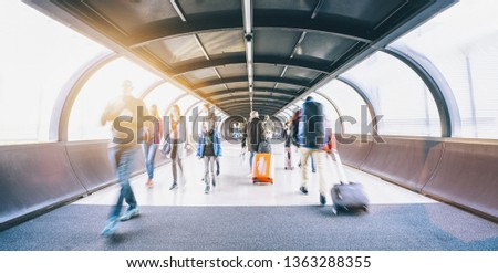 crowd of commuters rushing through an escalator in airport terminal  #1363288355