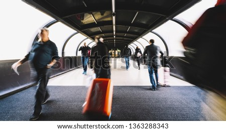 crowd of commuters rushing through in a airport terminal tunnel #1363288343