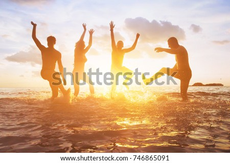 crowd of friends having fun in the water at sunset, silhouettes of happy people enjoying summer holidays #746865091