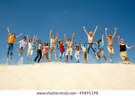 Crowd of friends jumping on sandy beach with their arms raised against blue sky