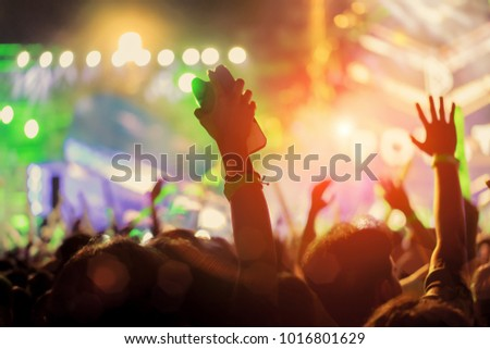 Crowd of hands up concert stage lights and people fan audience silhouette raising hands in the music festival rear view with spotlight glowing effect #1016801629