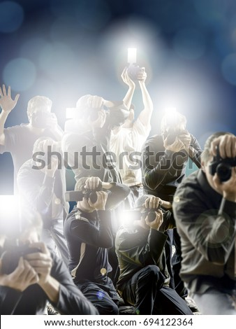 Crowd of paparazzi with flashing cameras in front a dark blue background.