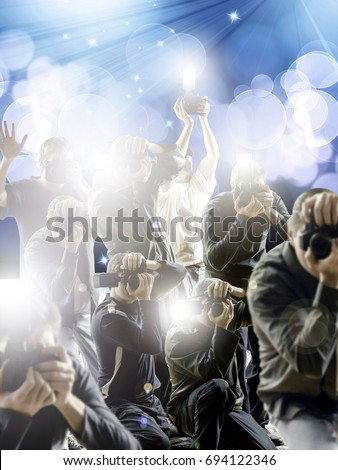 Crowd of paparazzi with flashing cameras in front a flash bright blue background.