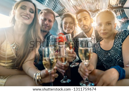 Crowd of party people in a limo with drinks, woman and men having fun