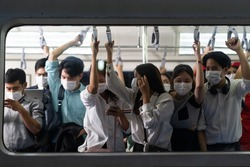 Crowd of passengers on Urban Public Transport Metro. Asian people go to work by public transport. Face Mask protection against virus. Covid-19, coronavirus pandemic