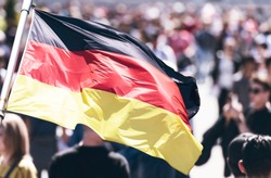 Crowd of People as Background and Flag of Germany